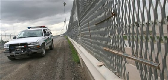 Image: Border Patrol car drives past portion of border fence