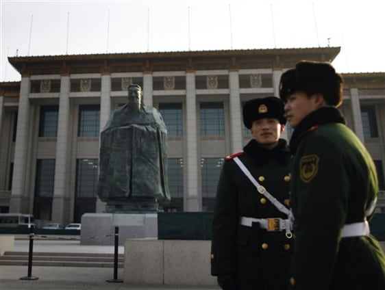 Image: Chinese paramilitary policemen stands guard in front of a sculpture of the ancient philosopher Confucius