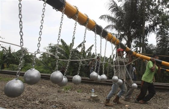 Image: Workers install a frame with concrete balls suspended on it above railway tracks in Bekasi, West Java, Indonesia