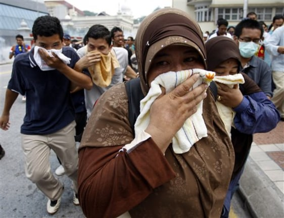 Image: Malaysian activists cover themselves with towels as they run away from tear gas