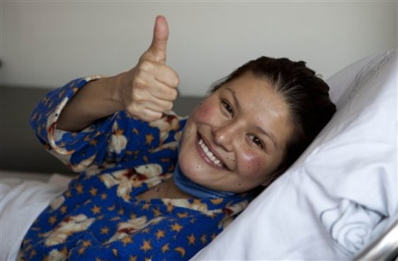 Image: Erika Hernandez, 28, gives a thumbs up from inside an ambulance after being discharged