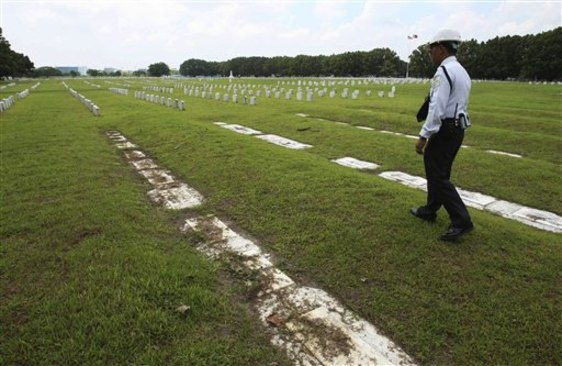 Image: A private guard walks along soil-covered grave markers at Clark Veterans Cemetery
