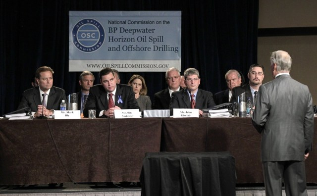 Image: Representatives from BP, Transocean and Halliburton sit at table during hearing