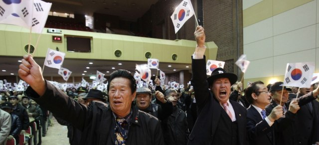 Image: South Koreans wave the national flag