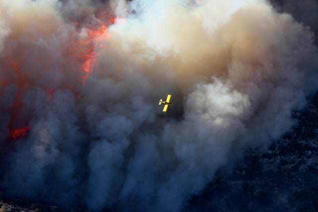 Image: A firefighting aircraft flies over a forest fire on Mount Carmel near Haifa