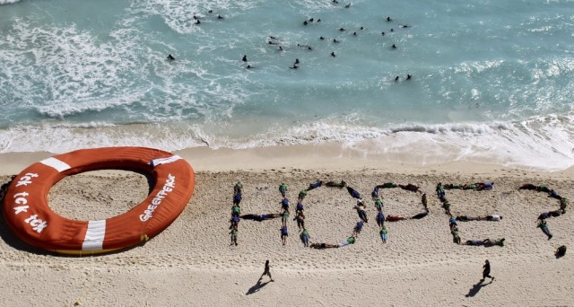 Image: Greenpeace activists spell out 'Hope?' on beach