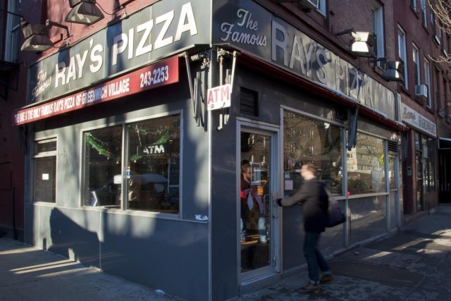 Image: Pedestrians stroll past Famous Ray's Pizza at West 11th St. and 6th Avenue in New York.