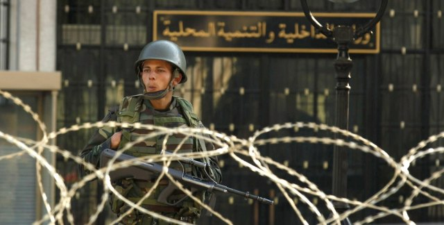 Image: An army soldier stands guard behind a wire fence cordon outside the interior minister's office in Tunis