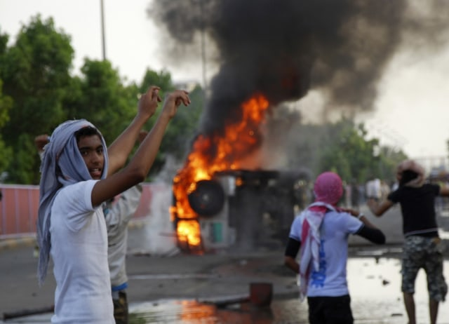 Image: Protesters watch after setting a government vehicle ablaze during clashes with police in Aden