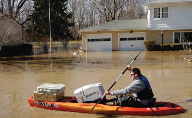 Image: Kayaker in flooded neighborhood