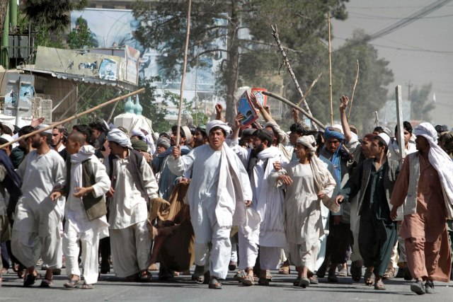 Image: Afghan protestors walk with sticks, as they carry a wounded colleague during a demonstration to condemn the burning of a copy of the Muslim holy book by a U.S. Florida pastor, in Kandahar southern of Afghanistan