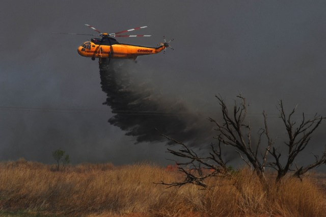Image: A helicopter drops water on a wildfire in Texas