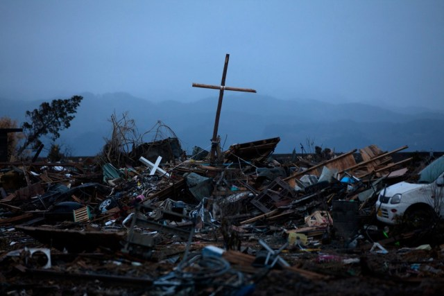 Image: A cross stands in the debris where a church used to be