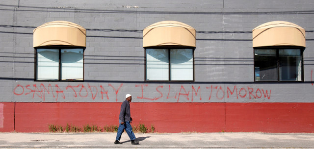 Image: Man walks by graffiti-covered wall in Portland, Maine