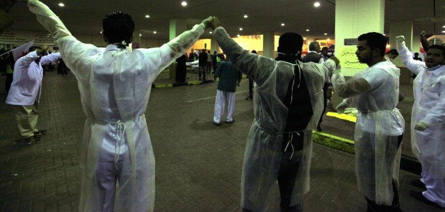 Image: Doctors form a human chain fearing an attack by riot police in Manama