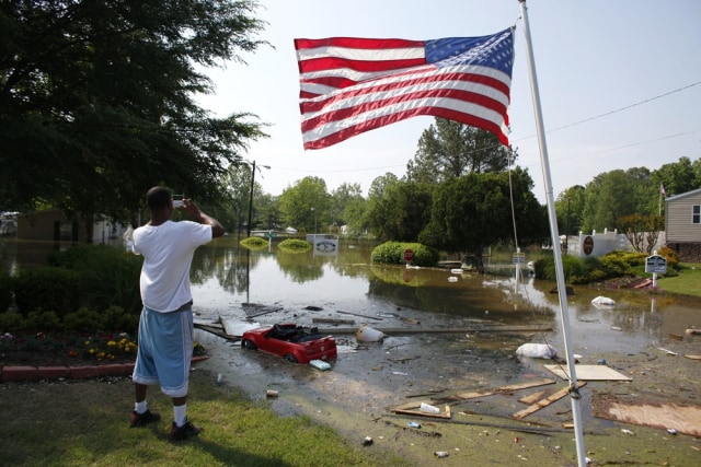 Image: A man takes a picture of a flooded mobile home park as floodwaters slowly rise in Memphis