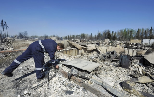 Image: A fire fighter searches for hot spots at a destroyed neighborhood in Slave Lake