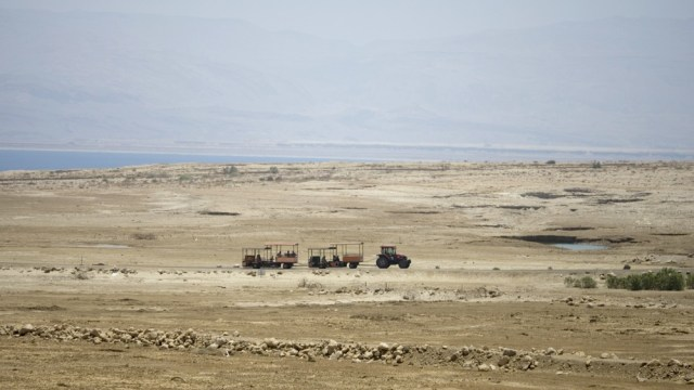 Image: Tractor transports Dead Sea visitors through area that once was water