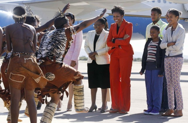 Image: Michelle Obama is welcomed by traditional dancers as they arrive in Gaborone, Botswana