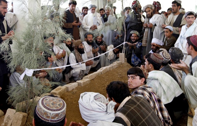 Image: Afghans pray over the grave of Ahmad Wali Karzai in his family's ancestral village of Karz