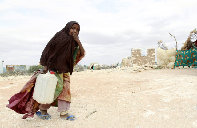 Image: An internally displaced Somali girl carries a jerry-can of water in Galkayo, northwest of Somalia's capital Mogadishu