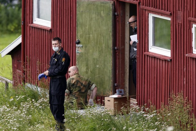 Image: Officials search a farm rented by Breivik in Rena