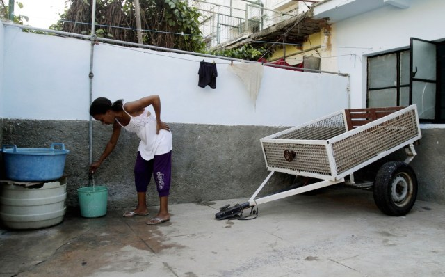 Image: Yusdany Simpson collects water in her home in Havana, Cuba