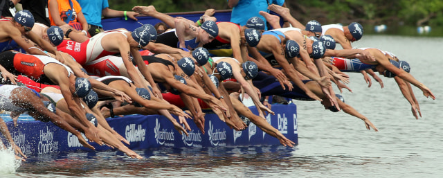 Image: Competitors dive into the water at the start of the men's elite race at the Hy-Vee Triathlon