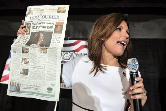 Image: Michele Bachmann holds up a copy of the local paper in Waterloo, Iowa