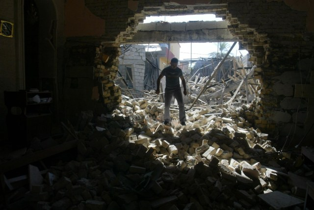 Image: An Iraqi man inspects the rubble of the Mar Afram Syriac Orthodox Church in Kirkuk