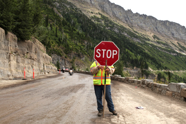 Image: Jennifer Goffard stops traffic from ascending Going-to-the-Sun Road as vehicles travelling in the opposite direction descend the road in Glacier National Park, Montana