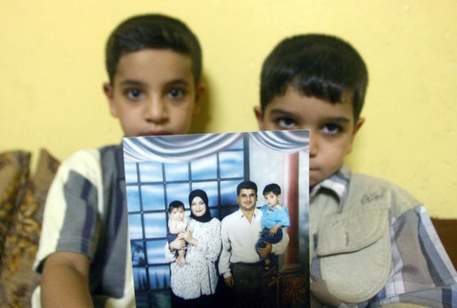 Image: This file picture taken on July 20, 2005 shows Hassan (L) sitting with his younger brother Ali as they show off a family photo of them posing with their father Baha Mousa and their mother, at their home in Basra, 500 kms south of Baghdad.