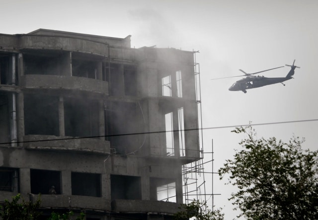 Image: A military helicopter belonging to coalition forces flies around a building during a gunbattle with Taliban militants in Kabul