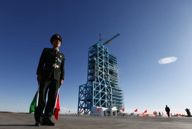 Image: Chinese soldier stands beside Long March II-F rocket loaded with China's unmanned space module Tiangong-1 at the launch pad in the Jiuquan Satellite Launch Center