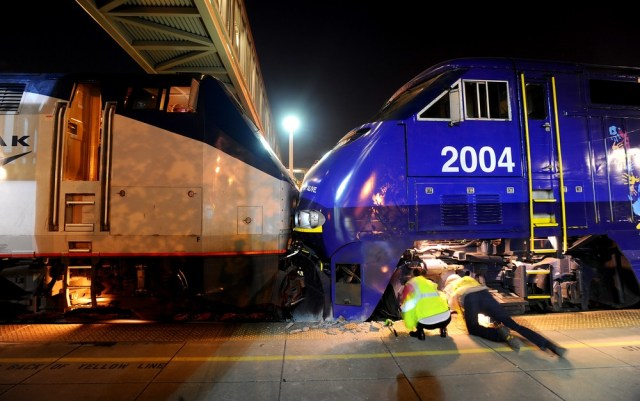 Image: Amtrak workers examine a train collision at an Oakland, Calif., station on Wednesday