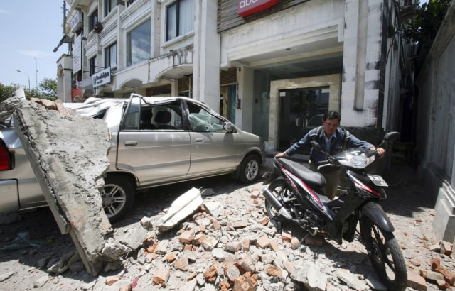 Image: A man pushes his motorbike away in the fallen debris of a building damaged by an earthquake in Kuta, Bali, Indonesia.