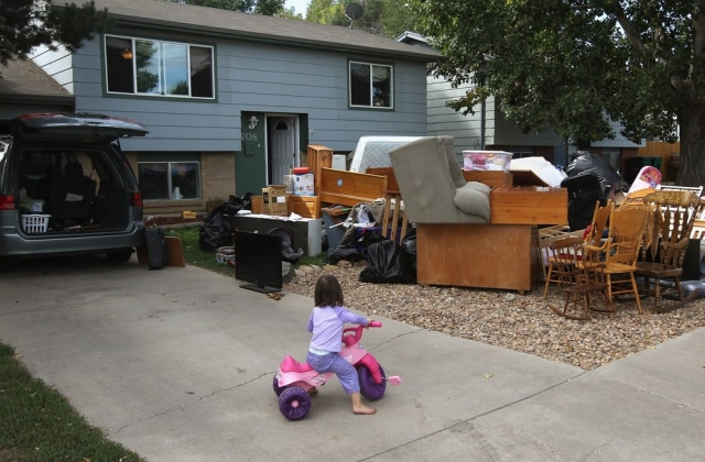 Image: Caitlin Barbiere plays in the driveway as her family's possessions sit piled nearby on Oct. 5 in Miliken, Colo.