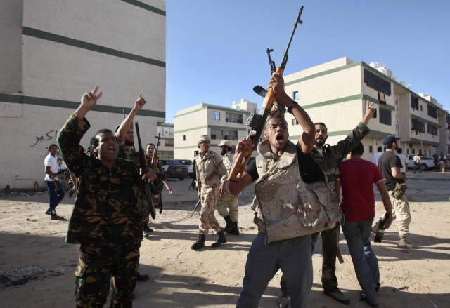 Image: Anti-Gaddafi forces shout during a gun battle with Gaddafi's supporters in the Abu Salim neighbourhood in Tripoli