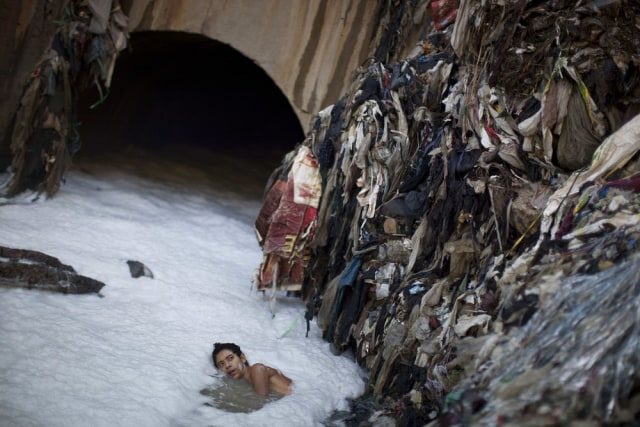 Image: Miner looks for gold in landfill drain