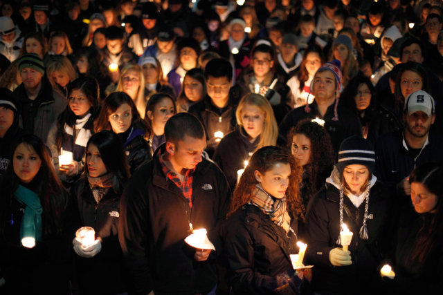 Image: People gather in front of the Old Main building for a candlelight vigil on the Penn State campus Friday in State College, Pa.