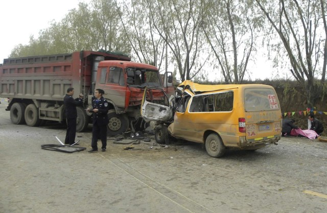 Image: Policemen inspect a school bus and a truck at a traffic accident site in Gansu Province, China