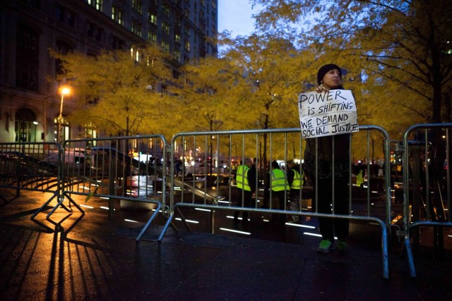 Image: A solitary Occupy Wall Street protestor holds a sign outside a nearly empty Zuccotti Park early on Wednesday