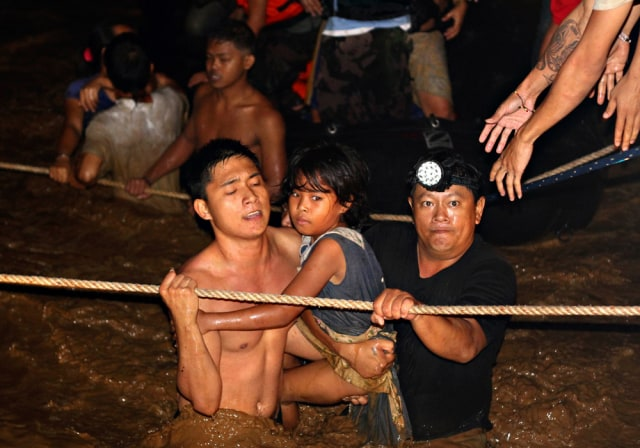 Image: Residents are rescued by volunteers following a flash flood in Cagayan de Oro city, Philippines