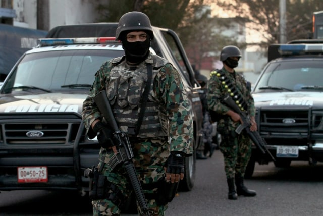 "Image: Mexican marines stand guard in front of the inter-municipal police station during the operation ""Veracruz Safe"" in Boca del Río, Veracruz State, Mexico."