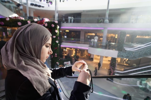 Image: A woman takes photographs at Morocco Mall near Casablanca