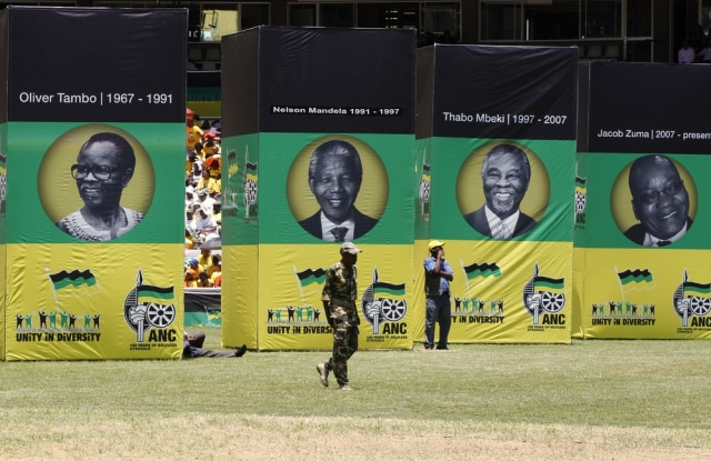 Image: A man in military uniform walks in front of posters depicting faces of former ANC presidents