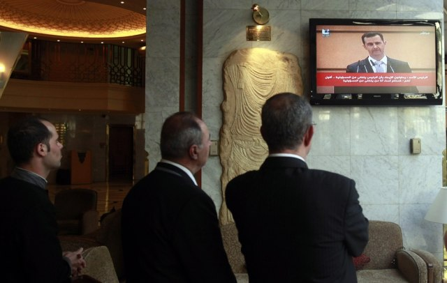 Image: Syrians watch on TV Syrian President Bashar Assad making a speech