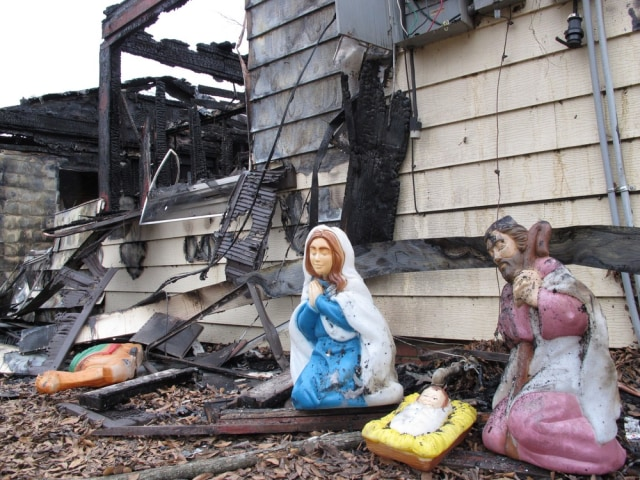 Image: Soot covers charred Christmas decorations outside the home of Janice Robbins near Conway, Ark.