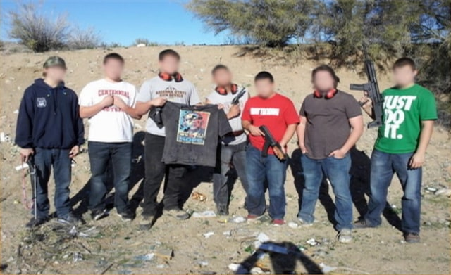 Image: Photo showing a group of men with guns posing with a bullet-ridden image of Barack Obama's face and posted on Facebook.