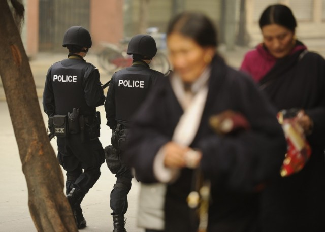 Image: Armed police patrol a street in Chengdu, China, as ethnic Tibetans walk past